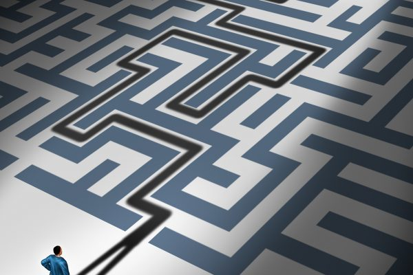 Solving Problems and problem solver business concept as the cast shadow of a businessman navigating through a complicated maze to freedom as a financial metaphor for predicting the future through leadership expertise and management skills.